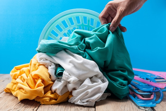 Dé sostener el lavadero sucio en cesta que se lava en el tablón de madera, fondo azul.