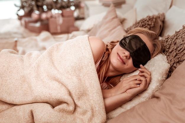 Debajo de una manta gruesa. chica de pelo claro pacífica durmiendo sobre un montón de almohadas mientras tiene máscara negra para dormir en
