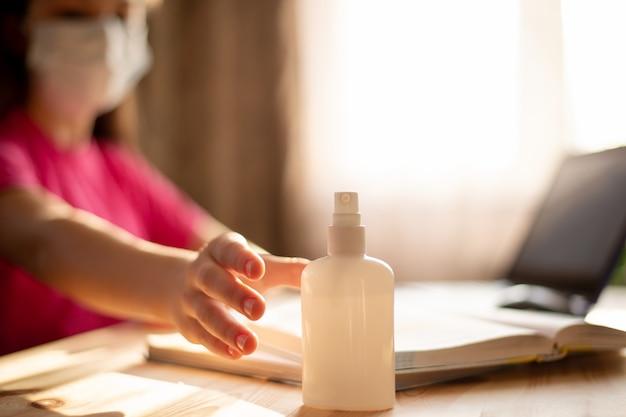 Deberíamos limpiarnos las manos regularmente. la niña usará desinfectante para manos mientras aprende a distancia para limpiarse las manos, el teclado de una computadora portátil y otras superficies