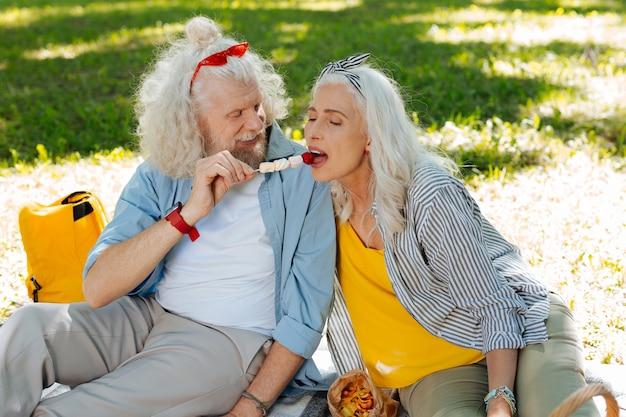 Debes intentar. buen hombre feliz alimentando a su esposa mientras hace un picnic junto con ella