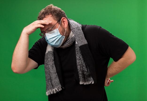 Débil con la cabeza baja, varón enfermo de mediana edad vistiendo máscara médica y bufanda poniendo la mano en la frente
