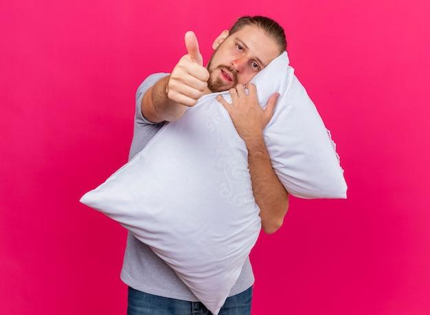 Débil joven apuesto enfermo eslavo abrazando la almohada poniendo la cabeza sobre ella mirando a la cámara mostrando el pulgar hacia arriba aislado sobre fondo carmesí