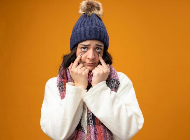 Débil joven caucásica enferma vistiendo bata gorro de invierno y bufanda mirando a la cámara tirando hacia abajo los párpados aislados sobre fondo naranja con espacio de copia