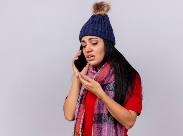 Débil joven caucásica enferma vistiendo gorro de invierno y bufanda hablando por teléfono manteniendo la mano en el aire mirando hacia abajo aislado sobre fondo blanco con espacio de copia