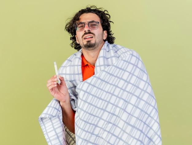 Débil joven caucásico enfermo con gafas envuelto en plaid sosteniendo un termómetro mirando a la cámara aislada sobre fondo verde oliva