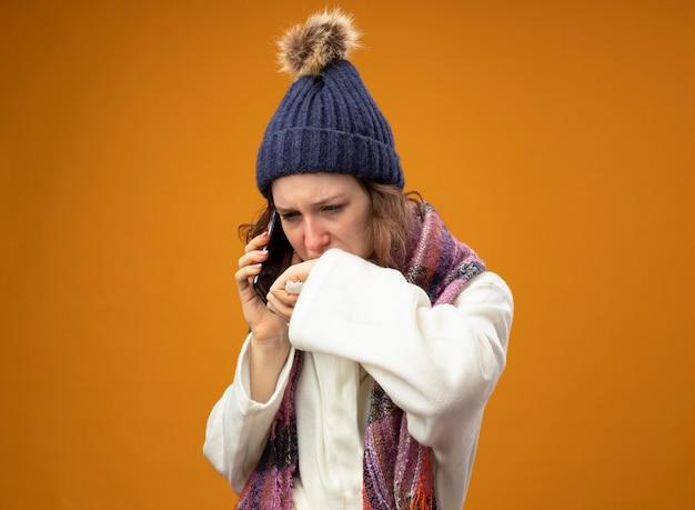 Débil joven enferma mirando hacia abajo vistiendo túnica blanca y gorro de invierno con bufanda habla por teléfono limpiando la boca con la mano aislada en naranja