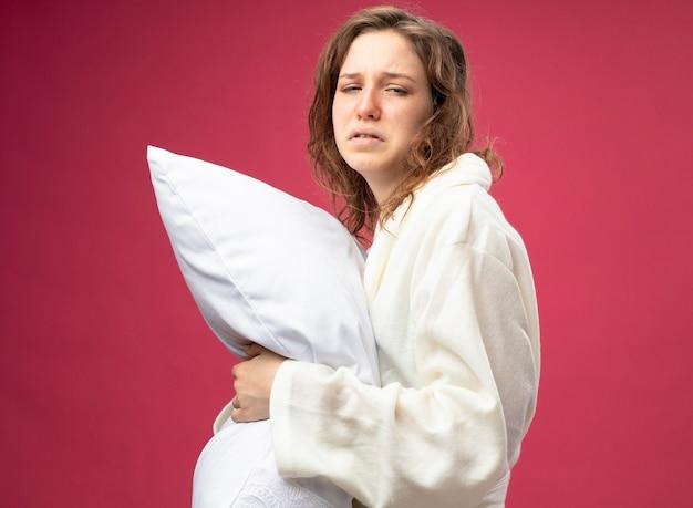 Débil joven enferma mirando al frente vistiendo bata blanca almohada abrazado aislado en rosa