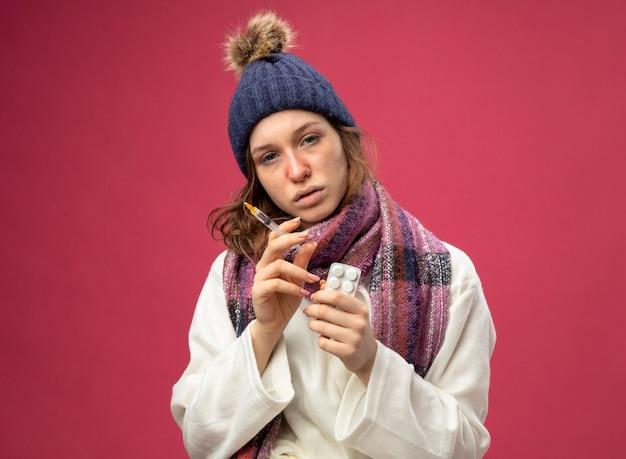 Débil joven enferma mirando al frente vistiendo bata blanca y gorro de invierno con bufanda sosteniendo una jeringa con pastillas aisladas en rosa