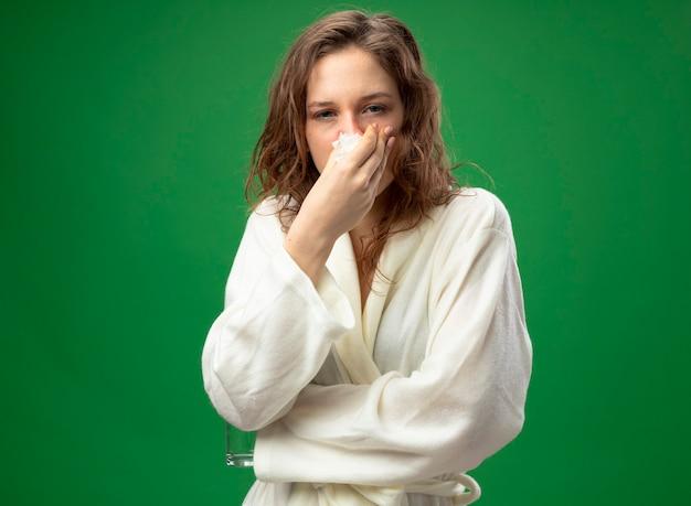Débil joven enferma mirando al frente vistiendo túnica blanca limpiando la nariz con una servilleta aislado en verde
