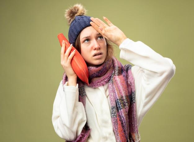 Débil joven enferma mirando hacia arriba vistiendo túnica blanca y gorro de invierno con bufanda poniendo una bolsa de agua caliente en la mejilla poniendo la mano en la frente aislada en verde oliva