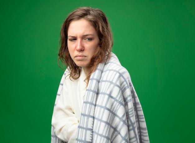 Débil joven enferma mirando a un lado vistiendo túnica blanca envuelta en cuadros aislados en verde