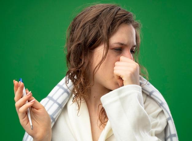 Débil joven enferma mirando de lado vistiendo túnica blanca envuelta en plaid sosteniendo el termómetro y agarró la nariz aislada en verde