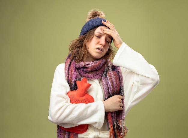 Débil joven enferma con los ojos cerrados vistiendo túnica blanca y gorro de invierno con bufanda sosteniendo una bolsa de agua caliente poniendo la mano en la frente aislada en verde oliva
