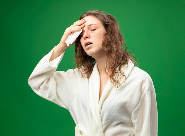 Débil joven enferma con los ojos cerrados vistiendo túnica blanca secándose la frente con una servilleta aislado en verde