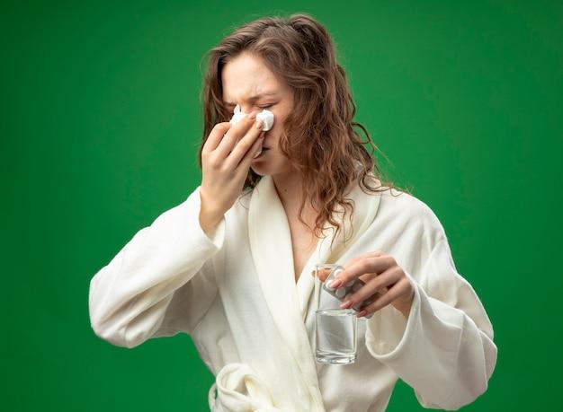 Débil joven enferma con los ojos cerrados vistiendo túnica blanca sosteniendo un vaso de agua limpiando la nariz con una servilleta aislado en verde