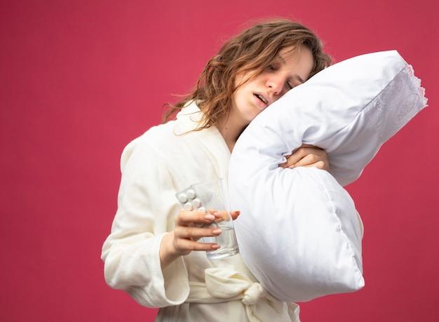 Débil joven enferma vistiendo túnica blanca almohada abrazado sosteniendo un vaso de agua