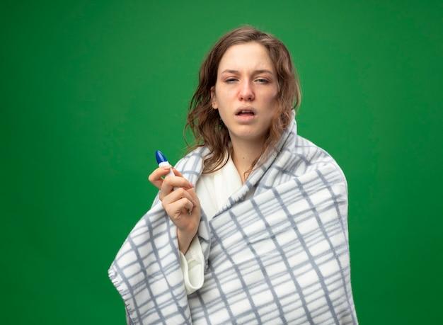 Débil joven enferma vistiendo túnica blanca envuelta en plaid sosteniendo termómetro aislado en verde
