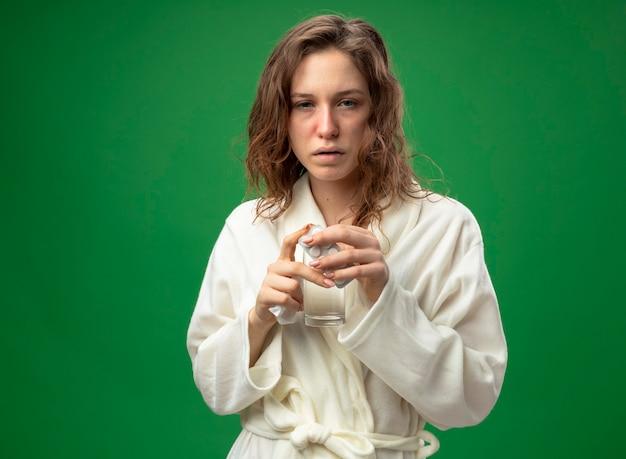 Débil joven enferma vistiendo túnica blanca sosteniendo túnica vaso de agua con pastillas aisladas en verde con espacio de copia