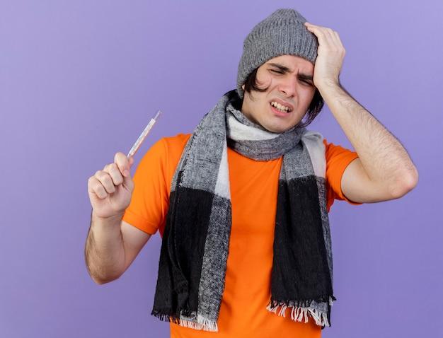 Débil joven enfermo vistiendo gorro de invierno con bufanda sosteniendo el termómetro y poniendo la mano en la cabeza dolorida aislado en púrpura