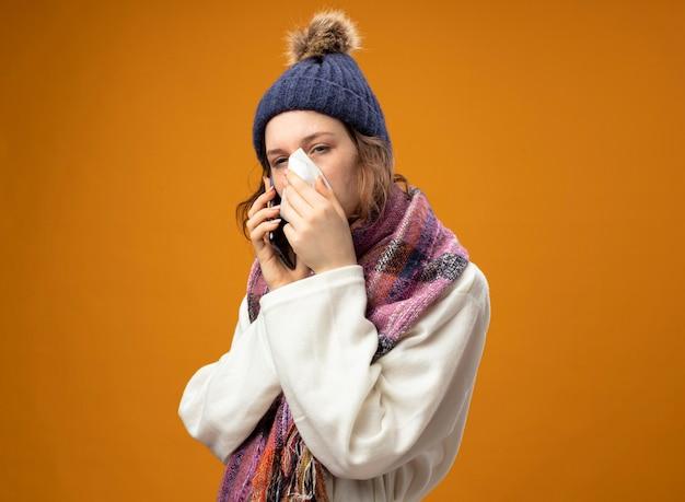 Débil niña enferma joven mirando a un lado vistiendo túnica blanca y gorro de invierno con bufanda habla por teléfono limpiando la nariz con una servilleta aislado en naranja