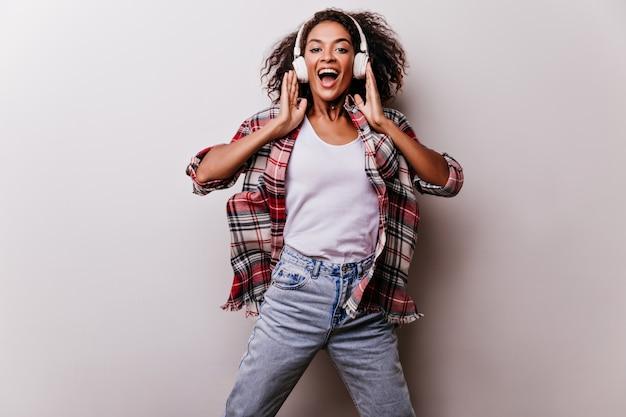 Debonair mujer riendo en jeans divertido baile. chica cantando entusiasta en auriculares posando en blanco