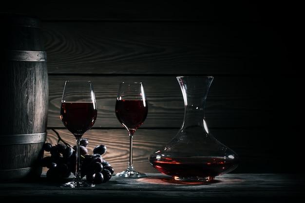 Decantador, dos copas de vino tinto y barril de madera.