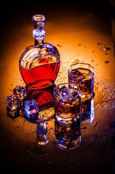Decantador y dos vasos con alcohol y hielo.