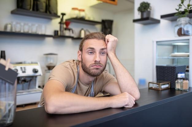 Decepción. hombre adulto joven frustrado en delantal de rayas y camiseta aburrido detrás de barra de bar en café