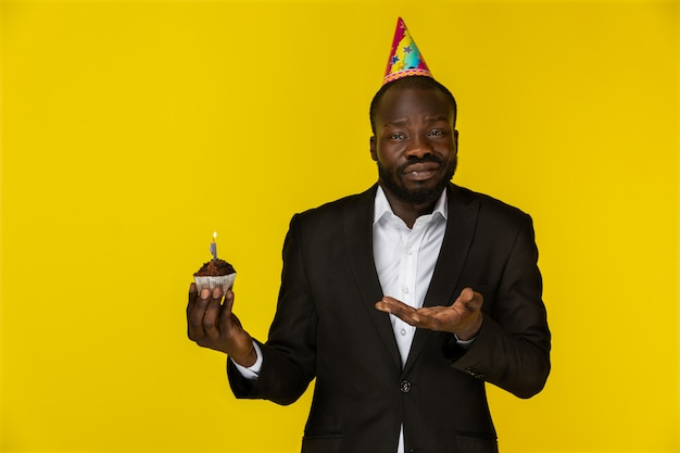 Decepcionado joven afroamericano en traje negro y sombrero de cumpleaños con velas encendidas