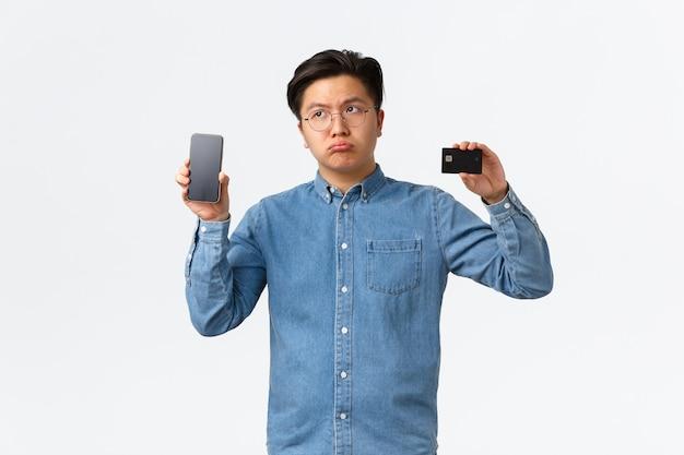 Decepcionado y triste chico asiático enfurruñado con gafas, suspirando arrepentimiento, quejándose de no tener una cuenta bancaria de dinero, mostrando la aplicación de banca electrónica en la pantalla del móvil y la tarjeta de crédito, fondo blanco.