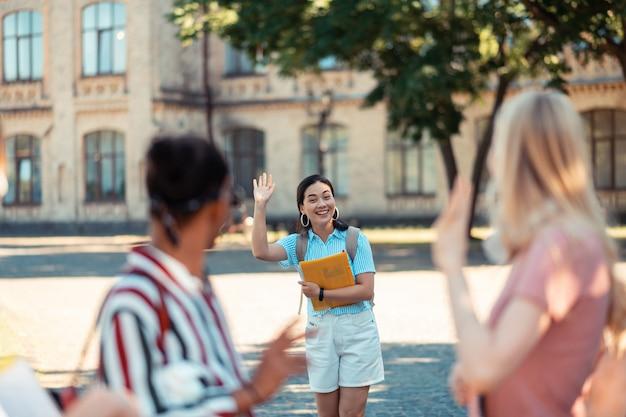 Decir hola. chica alegre con grandes pendientes en sus oídos saludando con la mano a los amigos que ve en el patio de la universidad.