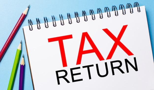 Declaración de impuestos de texto en un bloc de notas blanco con lápices sobre un fondo azul. concepto de negocio