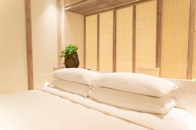 Decoración de almohadas blancas en la cama en el dormitorio del resort de hotel de lujo