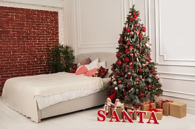 Decoración de año nuevo del dormitorio en el árbol de navidad de estilo escandinavo papá noel y cama con almohadas concepto de año nuevo hygge enfoque selectivo