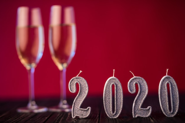 Decoración de año nuevo. dos gobelts con champán con decoración de navidad o año nuevo 2020 sobre fondo de luz roja