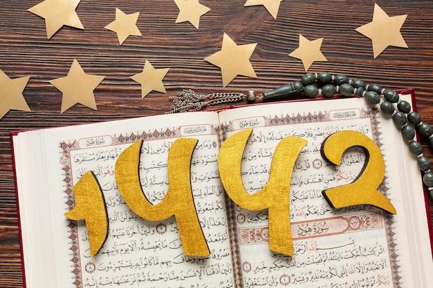 Decoración de año nuevo islámico con corán y estrellas.