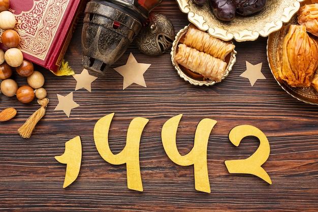 Decoración de año nuevo islámico con corán y pasteles tradicionales.