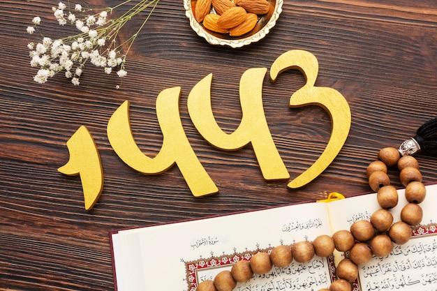 Decoración de año nuevo islámico con corán y pequeñas flores decorativas.
