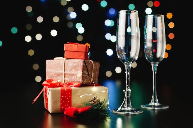 Decoración de año nuevo y navidad. flautas de champán, pequeños regalos y ramas verdes.