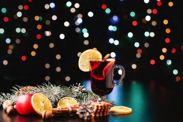 Decoración de año nuevo y navidad. gafas con vino caliente sobre mesa con naranjas, manzanas