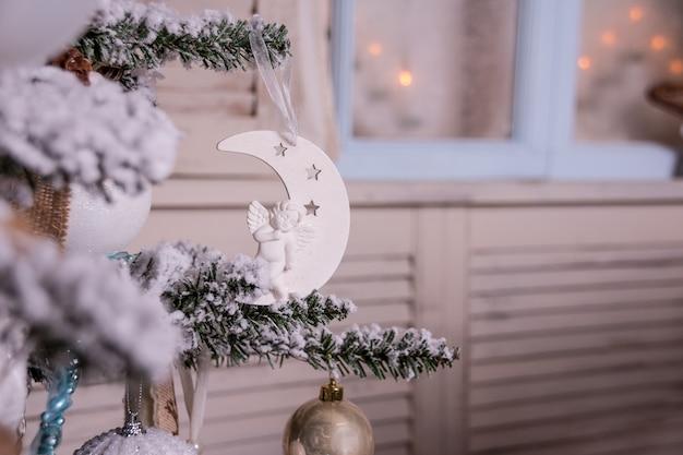 Decoración con árbol de navidad iluminado, regalos, chimenea, medias. navidad y año nuevo, decoración del hogar. estilo de decoración escandinava. interior, ambiente mágico. velas