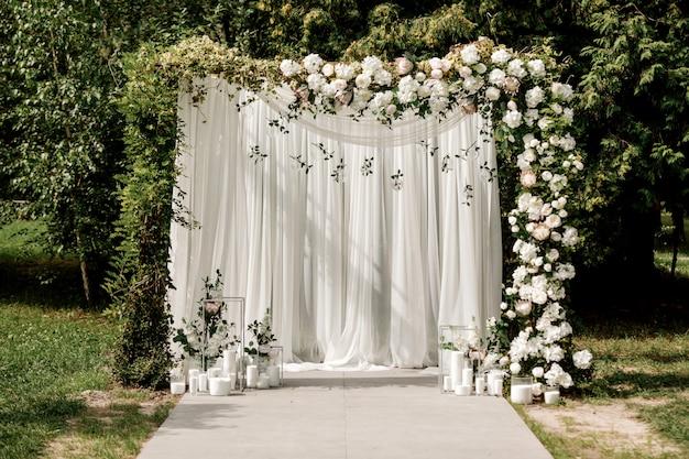 Decoración de arco de ceremonia de boda con rosas blancas y exterior verde