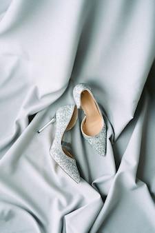 Decoración de boda con tela gris y tacones vista superior sobre un fondo gris texturizado