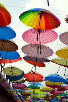 Decoración de calle con brillantes sombrillas contra el cielo.
