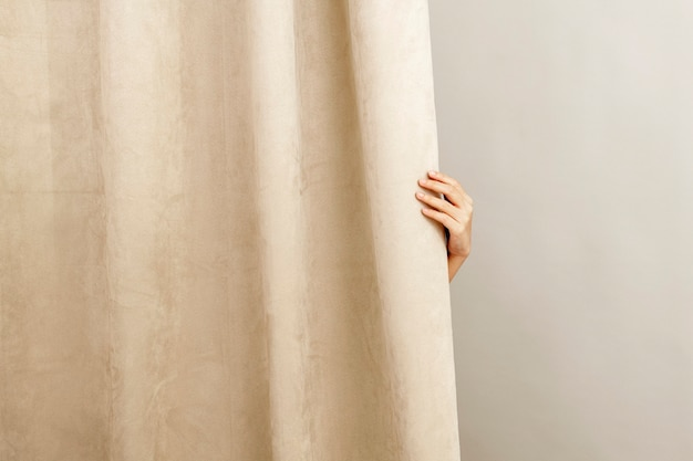 Decoración casera de cortina beige, con mano femenina