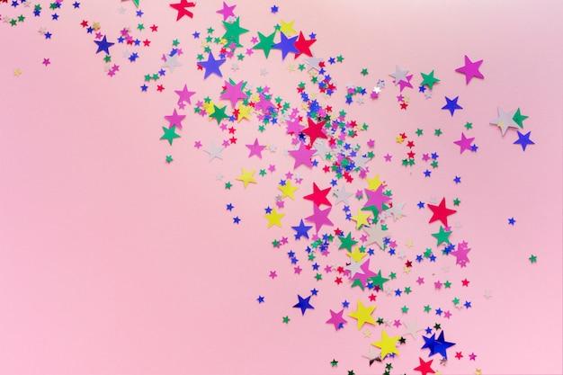 Decoración colorida de las estrellas del brillo, feliz navidad, feliz año nuevo aislado en fondo rosado. confeti en forma de estrellas
