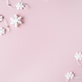 Decoración de copos de nieve de navidad blanca sobre fondo rosa. papel tapiz de navidad.