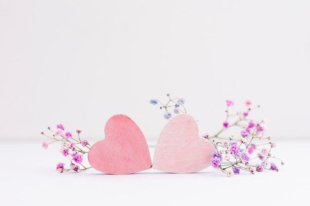 Decoración con corazones y flores sobre fondo blanco.