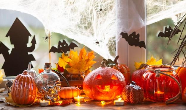 Decoración festiva de la casa en el alféizar de la ventana para halloween: calabazas, linternas de jack o, calaveras, murciélagos, telarañas, arañas, velas y una guirnalda: un ambiente acogedor y terrible.