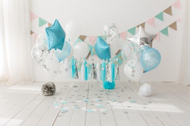Decoración festiva de fondo para la celebración de cumpleaños con pastel gourmet y globos azules.